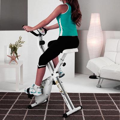 mujer haciendo bici estatica en casa para trabajar cardio